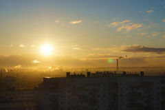 Soluppgång med ett bostadsområde av staden, en guld- timme, solsken som lite varstans översvämmas Arkivbild