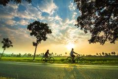Soluppgång med folk i cykel Fotografering för Bildbyråer
