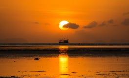 Soluppgång med moln och siluatefartyget Arkivbild