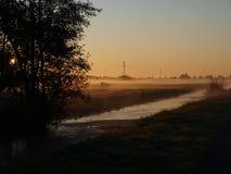 Soluppgång med morgondimma över ängarna av polder på Goudarak nästan gouda i Nederländerna royaltyfria foton