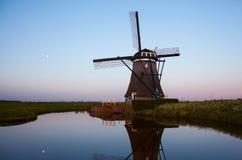 Soluppgång med traditionella holländska väderkvarnar reflekterade i stillheten w Royaltyfri Fotografi