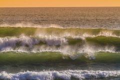 Soluppgång och att skina vinkar i havet Arkivbild