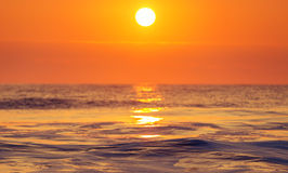 Soluppgång och att skina vinkar i havet Royaltyfria Bilder