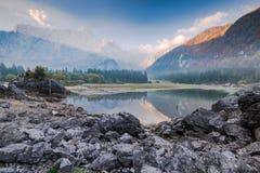 Soluppgång och dimma på Fusine sjön, Italien royaltyfri fotografi