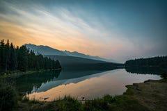 Soluppgång och dimmig morgon över monteringen Rundle på två Jack Lake in Royaltyfri Bild