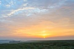 Soluppgång och grässlätt Arkivbild