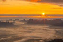 Soluppgång och mist på berget Arkivfoto