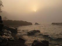 Soluppgång- och morgondimma på sjön Arkivbild