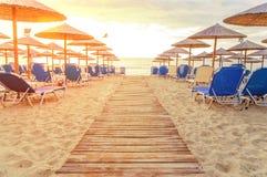 Soluppgång och stranden sunbed greven i morgonen med den brinnande solen Fotografering för Bildbyråer