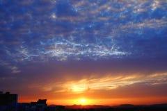Soluppgång på blåtten och den molniga himlen Fotografering för Bildbyråer