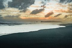Soluppgång på den berömda svarta sandstranden Reynisfjara i Island Blåsig morgon waves för wave för fokusförgrundshav färgrik sky fotografering för bildbyråer