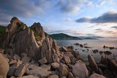 Soluppgång på den steniga kusten Arkivfoto