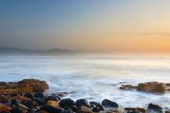 Soluppgång på den steniga stranden, östliga London, South Africa Arkivbilder