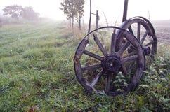 Soluppgång på dimmigt höstlandskap med två antika trähjul Fotografering för Bildbyråer