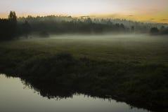 Soluppgång på fältet med dimma nära flodbanken Arkivbild