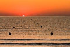 Soluppgång på havet med boj Arkivbild