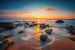 Soluppgång på havet vaggar och härliga moln royaltyfria foton