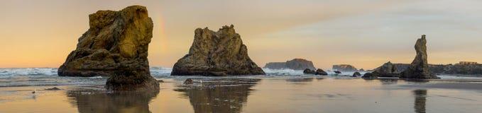Soluppgång på havstranden med klippor Arkivbild