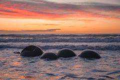 Soluppgång på Moeraki stenblock Arkivbilder