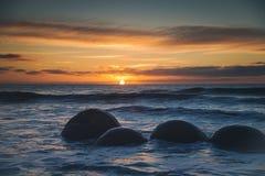 Soluppgång på Moeraki stenblock Royaltyfria Foton