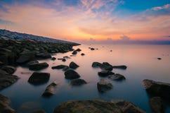 Soluppgång på mossigt vaggar nära havet med mjölkaktigt seende vatten Arkivbild