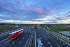 Soluppgång på motorwayen M1 med bilar i rörelse Royaltyfri Foto