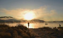 Soluppgång på sjön Kawaguchiko, folk som fiskar på ett fartyg, silhoue Arkivfoto