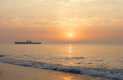 Soluppgång på sjösidan med en skeppsbrott Royaltyfri Bild