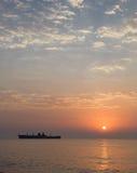 Soluppgång på sjösidan med en skeppsbrott Royaltyfria Foton