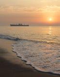 Soluppgång på sjösidan med en skeppsbrott Royaltyfria Bilder