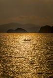 Soluppgång på stranden med det lilla fartyget Arkivfoto