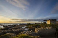Soluppgång på stranden med vaggar Fotografering för Bildbyråer