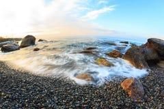 Soluppgång på stranden med vaggar och havet Arkivfoto