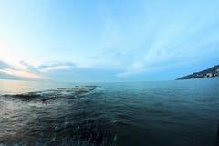 Soluppgång på stranden med vaggar och havet Royaltyfri Foto
