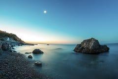 Soluppgång på stranden med vaggar och havet Arkivfoton