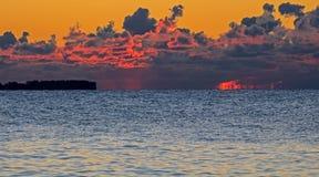 Soluppgång tänder upp stackmolnmoln över Lake Ontario arkivfoton