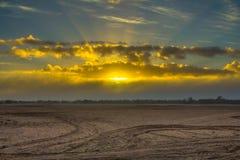 Soluppgång till och med moln ovanför plöjt fält Arkivbild