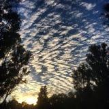 Soluppgång till och med molnen Arkivfoton