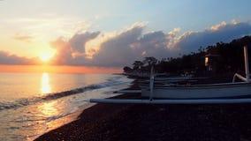 Soluppgång vid stranden med traditionella fartyg i Bali lager videofilmer