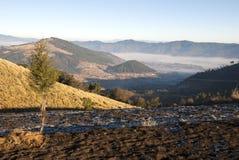 Soluppg?ngberg odlade med pittoreska byar i lantliga Guatemala, mist och frost Central America royaltyfri fotografi