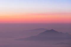 Soluppgångplats med det dimmiga berget Arkivbild