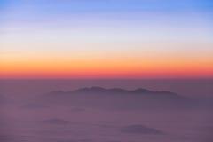 Soluppgångplats med det dimmiga berget Arkivfoton