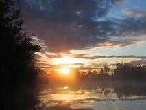 Soluppgångreflexion på morgonmistsjön Arkivfoton