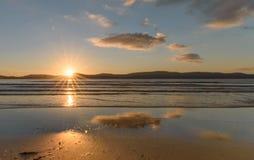 SoluppgångSeascape med reflexioner och Sunburst arkivfoto