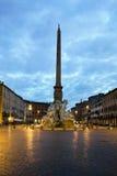 Soluppgångsikt av den Bernini obelisken och springbrunnen i Rome, Italien Royaltyfria Bilder