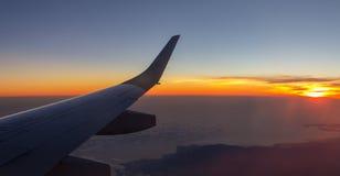 Soluppgångsikt från hyttventilen av ett flygplan under en tur royaltyfri foto