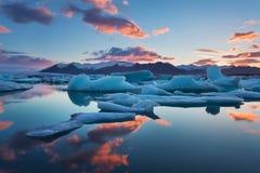 Soluppg?ng i Jokulsarlon Island islagun av jokulsarlon i morgonen i sommar eller vinter bl?a isberg fotografering för bildbyråer