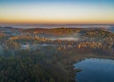 Soluppg?ng ?ver skogar och sj?ar - surrsikt fotografering för bildbyråer