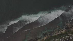 Soluppg?ngsurrl?ngd i fot r?knat av en lugna klippa och strand n?ra den Uluwatu templet, Bali, Indonesien arkivfilmer