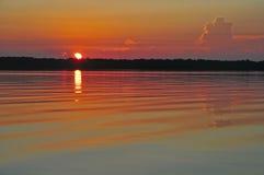 Soluppgång med reflexion i lugna vatten Arkivbild
